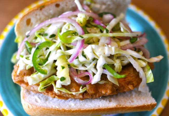 A Vegan Fried Chicken Sandwich featured on Namely Marly and topped with a savory slaw of of sliced jalapenos, pickled red onions, and high-quality olive oil.