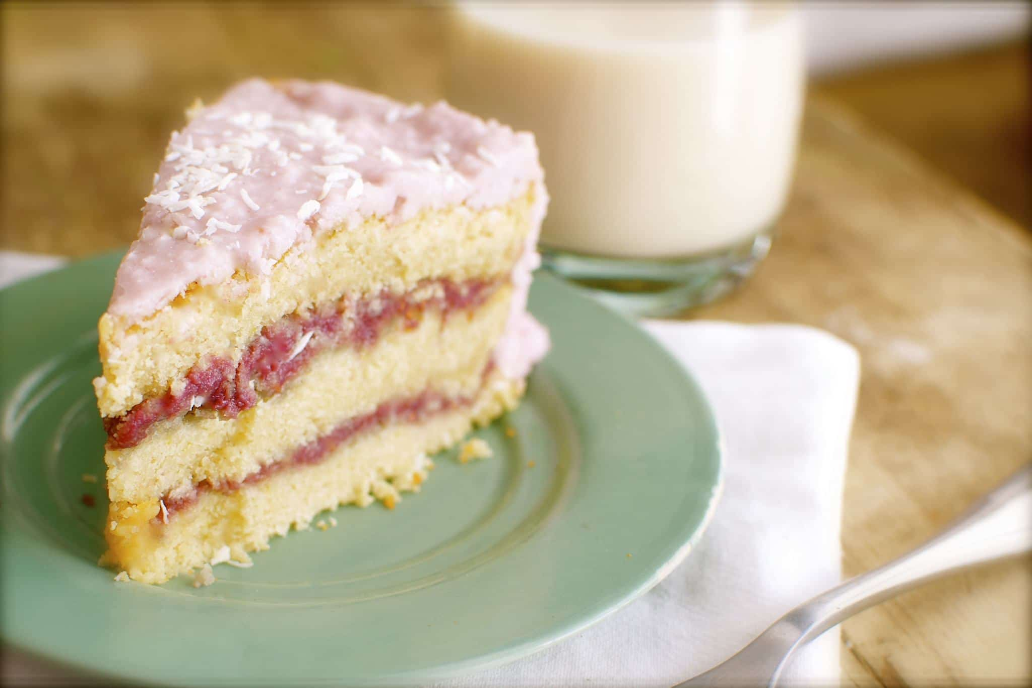 Pink coconut cream icing is lightly dusted with a layer of shredded coconut for this coconut cake.