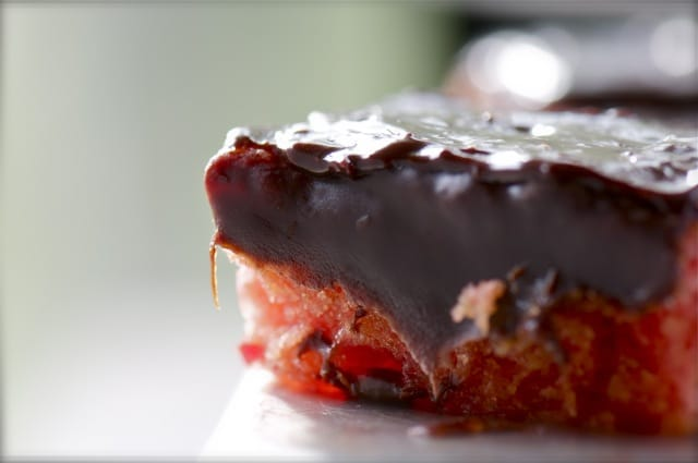 A straweberry cake topped with chocolate fudge icing is backlit by the morning sun.