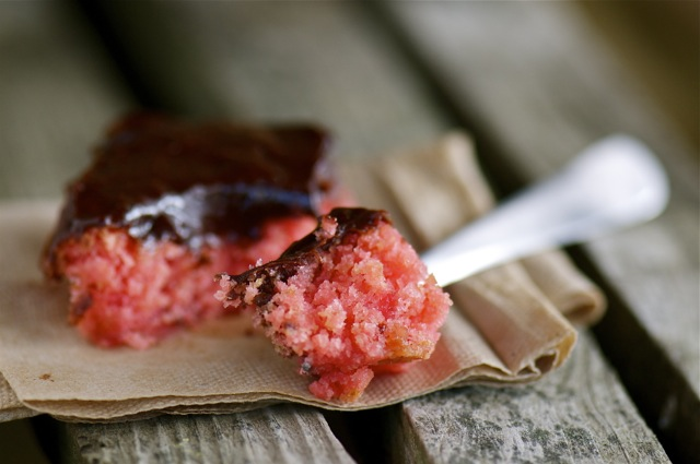 One slice of vegan Strawberry Cake has one bite sitting on a fork.