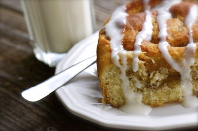 A Cinnamon Roll drizzled with frosting sits with a fork near a glass of soy milk.