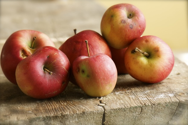 A photo of several organic apples on a bench