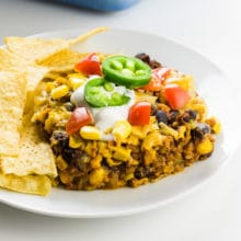 A closeup of a slice of a Mexican casserole on a plate surrounded by tortilla chips.