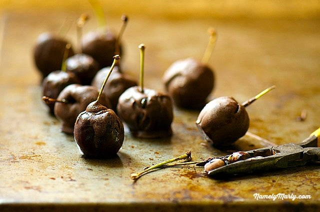 Fresh pitted cherries are dipped in chocolate and served with the stem for decoration.