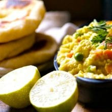 A serving dish full of chickpea curry sits next to naan bread and limes.