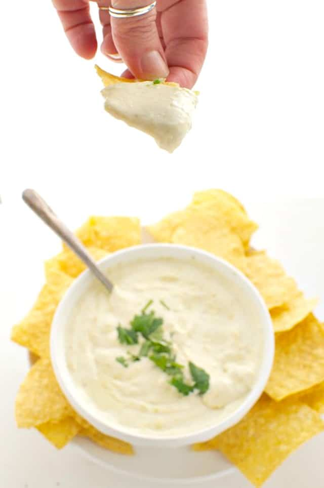 A hand holds a tortilla chip full of vegan queso dip. Below it is the rest of the bowl of the dip and more tortilla chips.