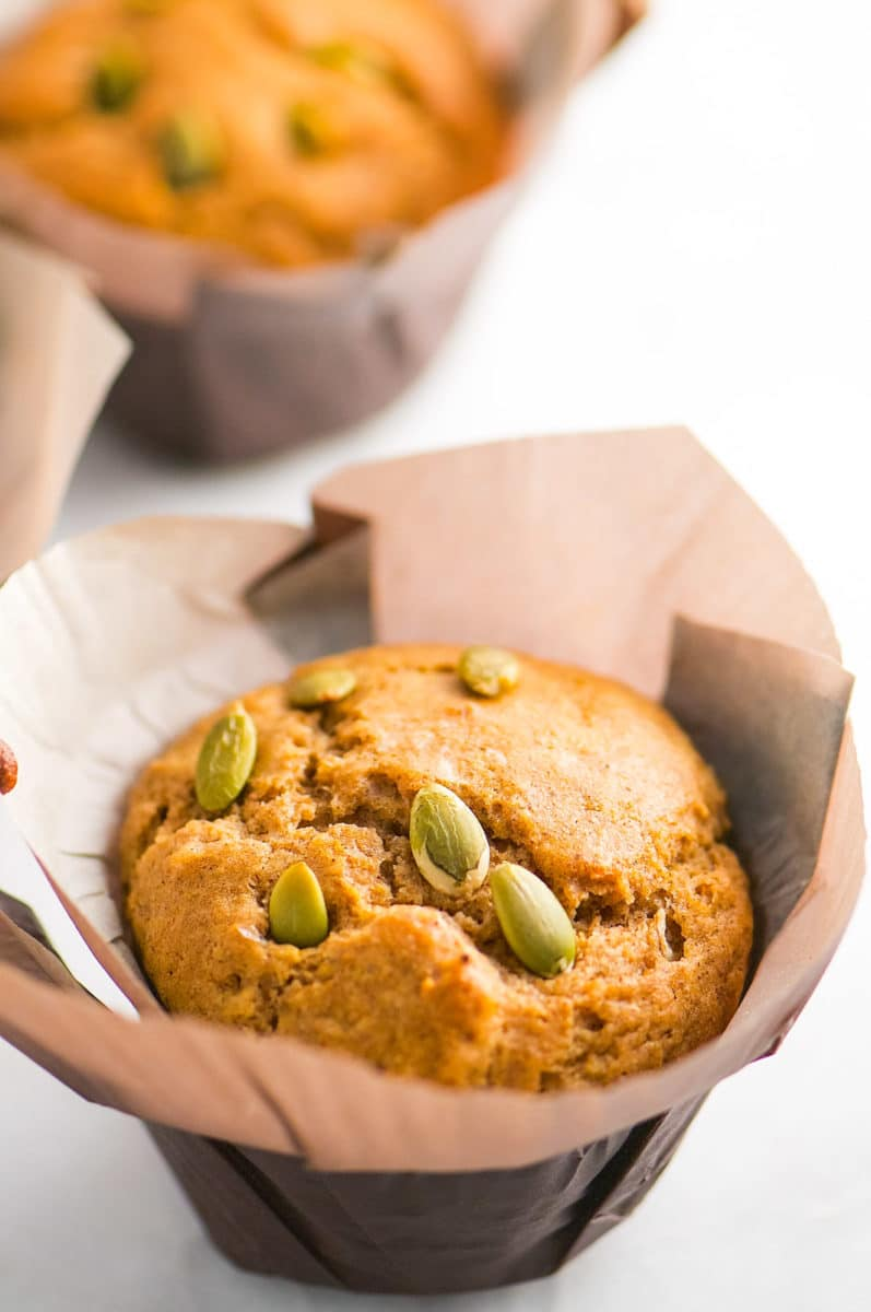 A closeup of a muffin with pumpkin seeds on top. The muffin is in a large brown paper.