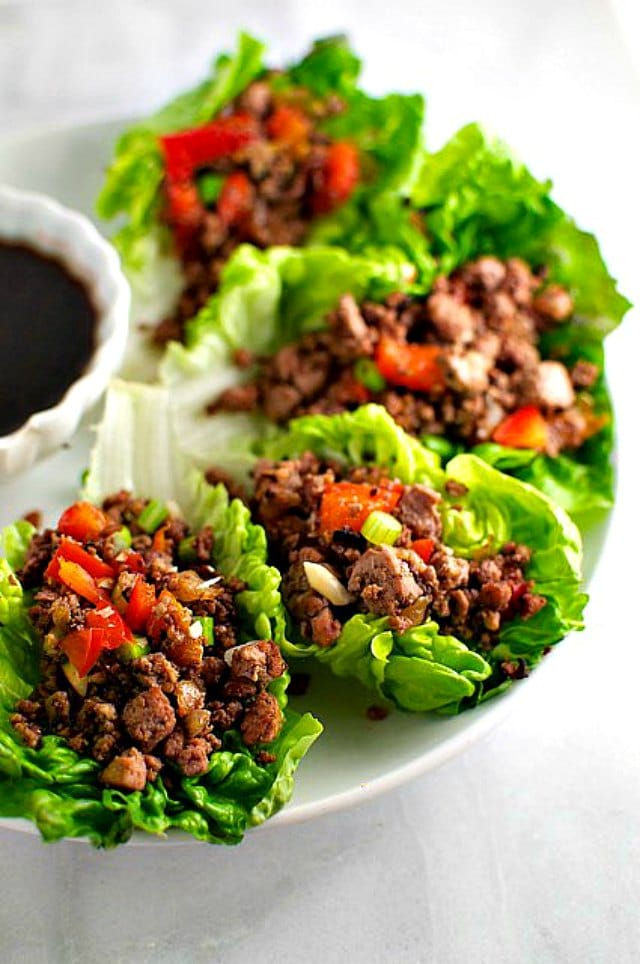 A platter of lettuce wraps filled with veggie filling and sitting next to a bowl of dipping sauce.