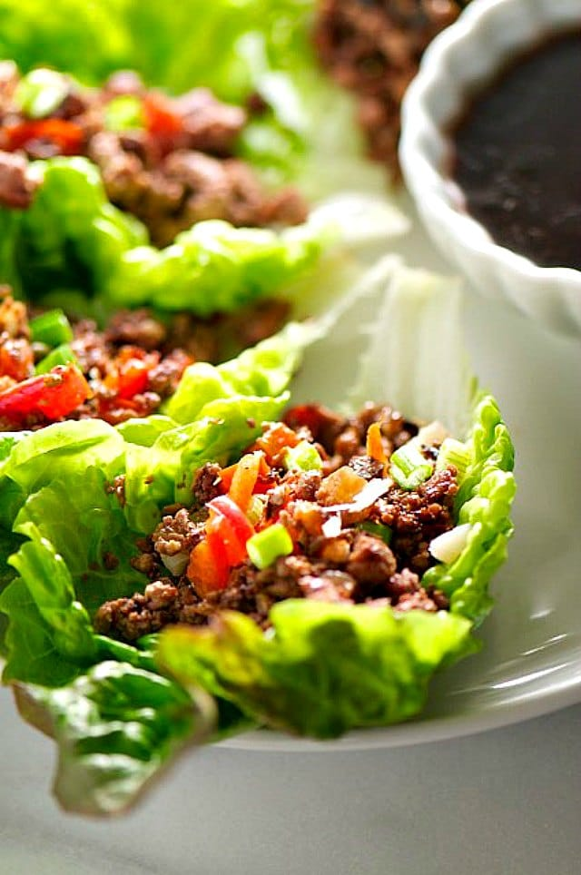 A close up of several vegetarian lettuce wraps filled with veggie filling next to a bowl of dipping sauce.