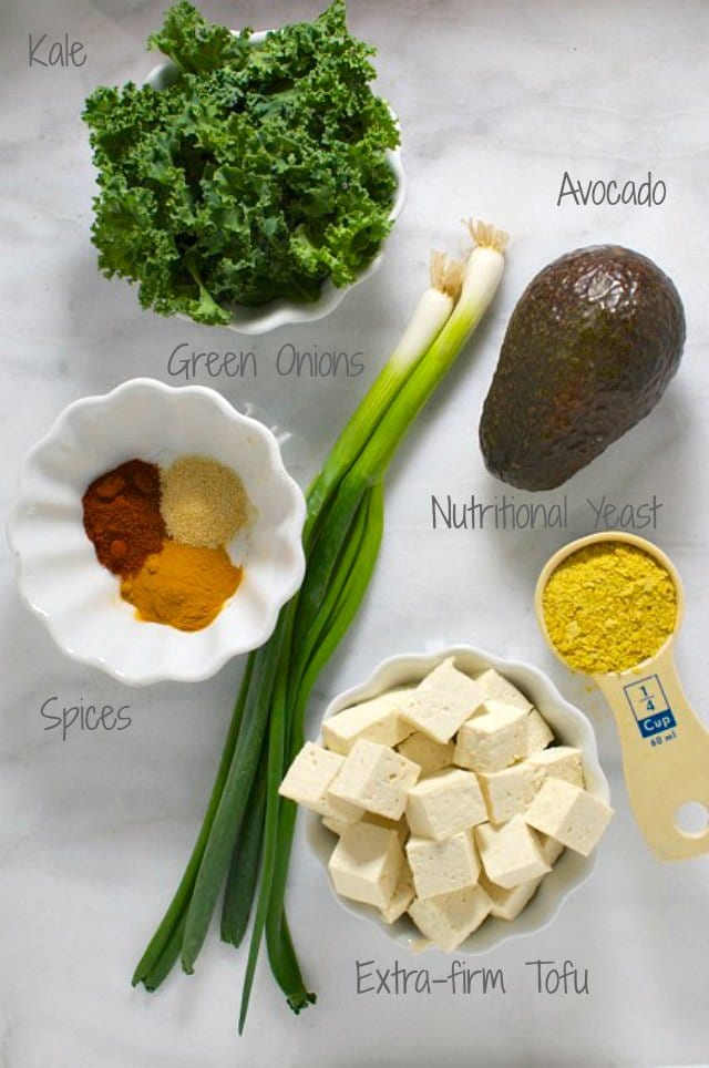 Looking down on ingredients for this tofu scramble, including tofu cubes, green onion, and more.