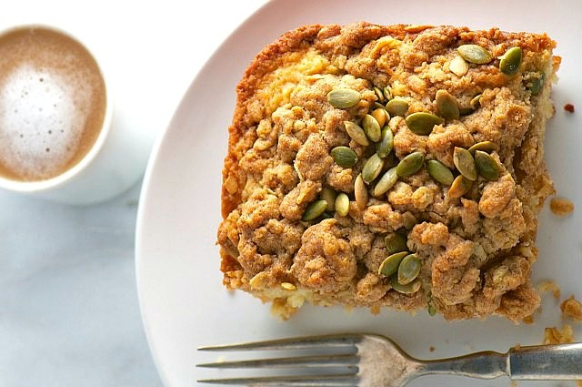Looking down on a slice of crumble pastry with a fork and a mug of creamy tea is beside it.