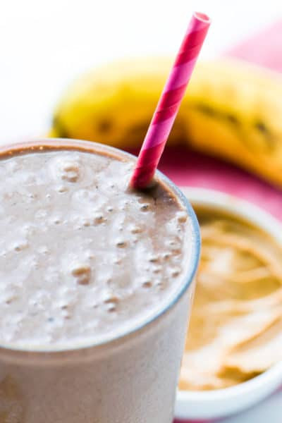 A closeup of a Chocolate Peanut Butter Protein Smoothie in a tall glass with a pink straw. A banana and bowl of peanut butter is blurred in the back.