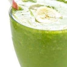 A a clear glass is full to the rim with green banana smoothie. A pink and white paper straw is on the side, and a slice of banana is in the middle of the smoothie.