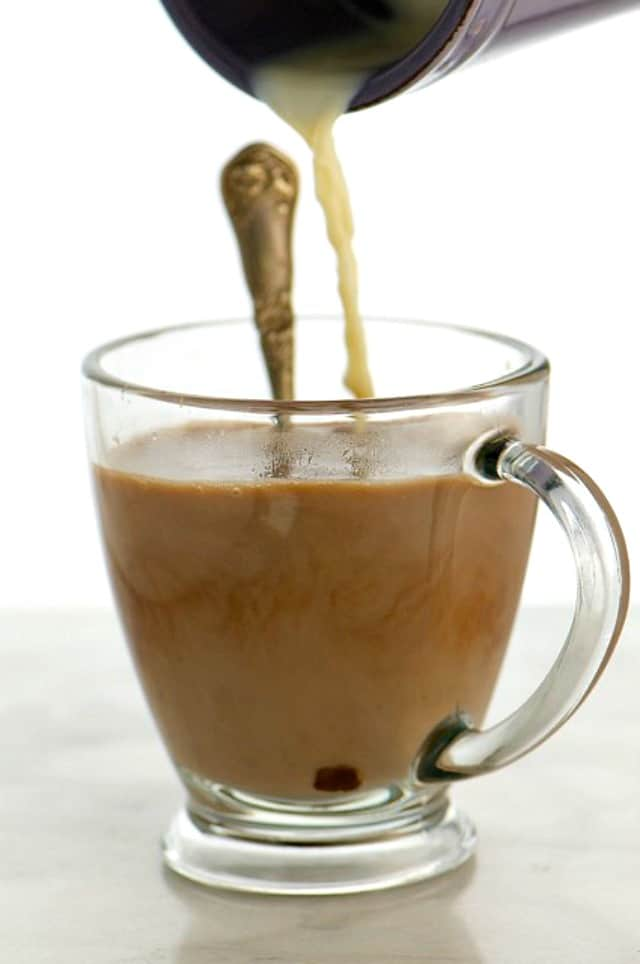 A container pours plant-based milk into a cup of cocoa with a spoon in it.
