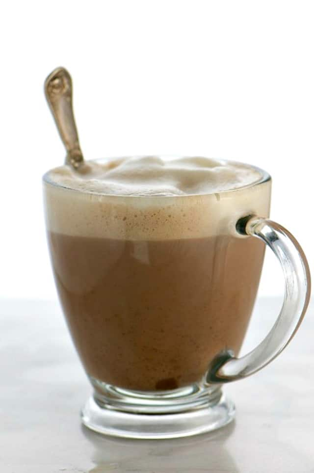 A glass mug full of hot cocoa with lots of frothy plant based milk at the top.