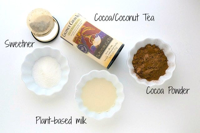 Looking down on the ingredients for this tea-infused hot cocoa, including cocoa powder, plant-based milk, and more.