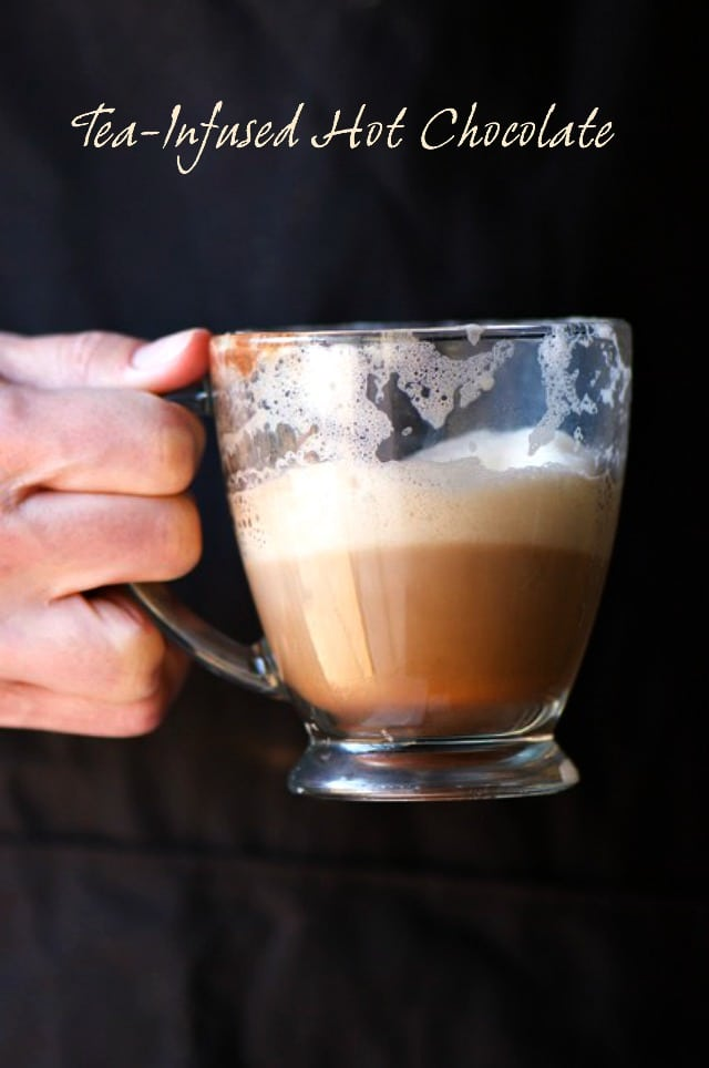 A hand holds a mug of half-full cocoa with frothy milk on the top.