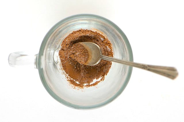Looking down on the cocoa mix at the bottom of the glass coffee mug. A spoon is in the cup as well.