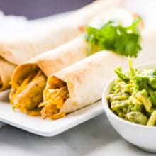 Vegan chicken taquitos are on a plate next to guacamole.