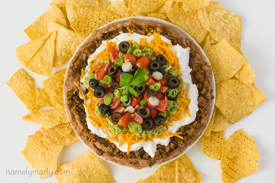 Looking down on a plate full of vegan 7 layer dip surrounded by tortilla chips.