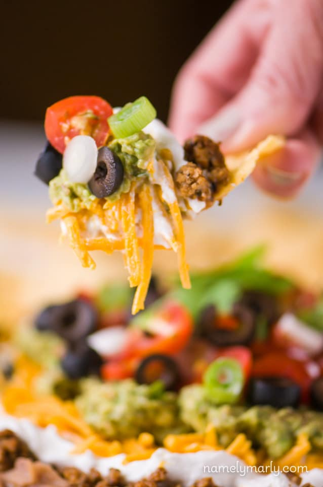 A hand holds a tortilla chip loaded with vegan seven layer dip. The plate of dip is sitting in the background.