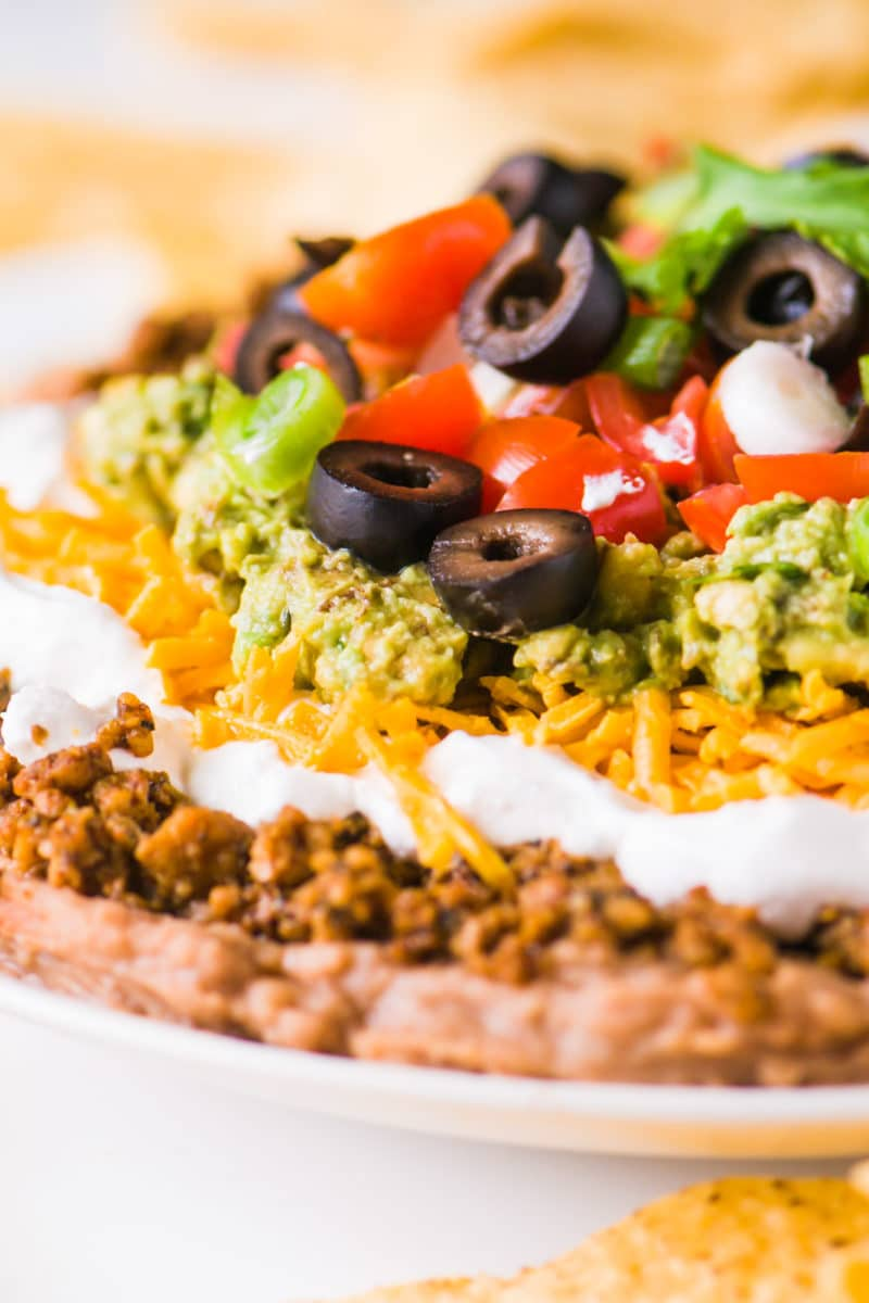 A close-up shot of vegan 7 layer dip shows layers of beans, veggie crumbles, and more toppings.