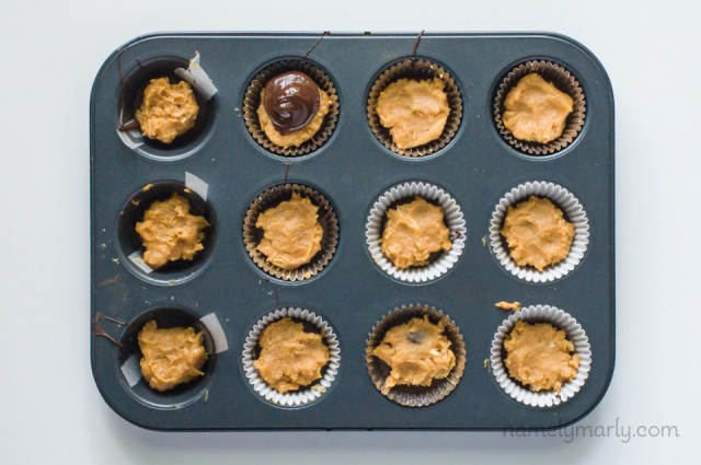 A tray of a mini muffin pan holds chocolate candies being made into peanut butter cups.