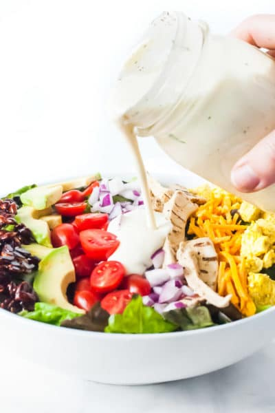 Vegan ranch dressing is poured over a bowl of salad topped with bacon flavored almond slivers, sliced avocados, sliced cherry tomatoes, chopped red onions, vegan cheddar, and tofu scramble.