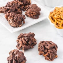 Several Chocolate-Covered Trail Mix Clusters on a white counter top with a bowl of pretzels, vegan marshmallows and more cookies behind them.