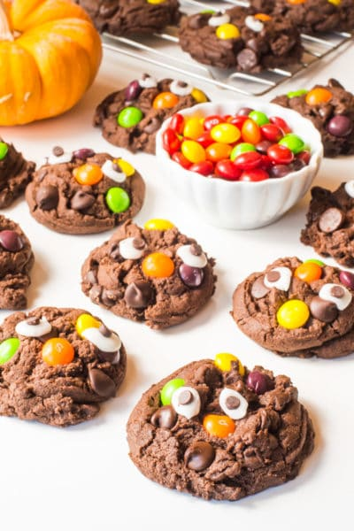 Several Halloween Monster cookies have candy eyes and colorful skittles on top. There's a bowl of the candies and a mini pumpkin beside them.