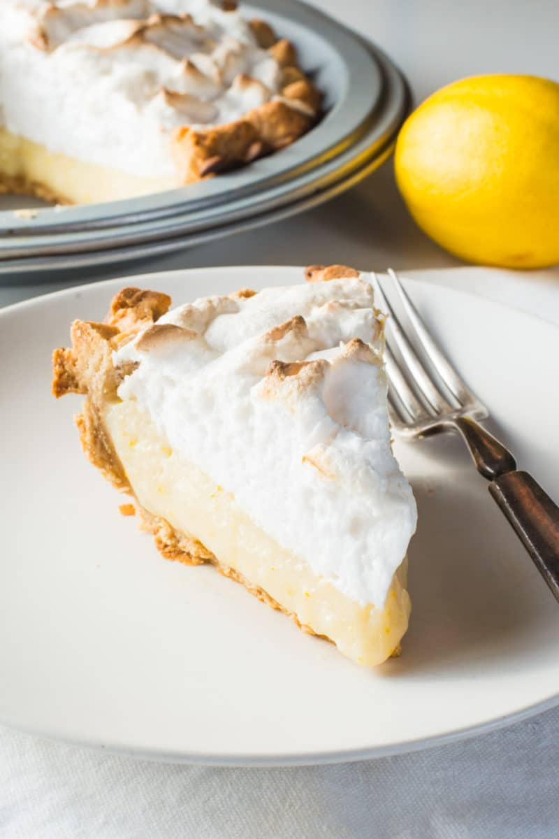 A slice of lemon pie on a plate with a  fork beside it. A lemon and the rest of the pie is behind it.