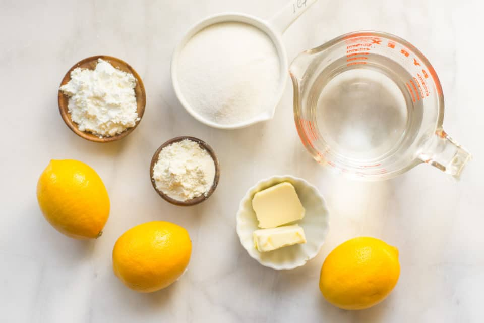 Looking down on ingredients on a counter, like sugar, water in a measuring cup, butter, lemons, etc.