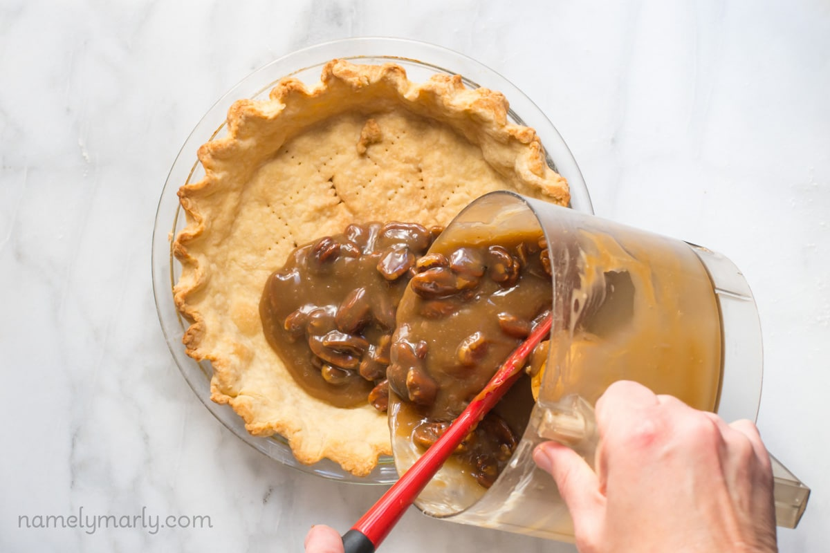 Pouring the custard into the prepared pie crust for this amazing Vegan Pecan Pie!