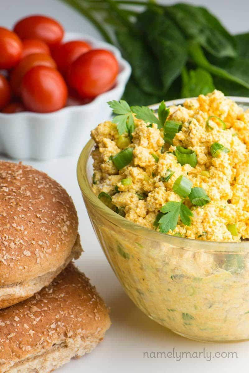 A bowl fun of vegan egg salad sits beside a stack of buns. Behind it is a bowl of cherry tomatoes and raw spinach.