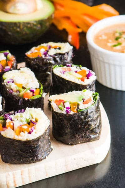 Several slices of vegan sushi with the dark nori on the outside sits by a bowl of spicy sweet peanut butter sauce.
