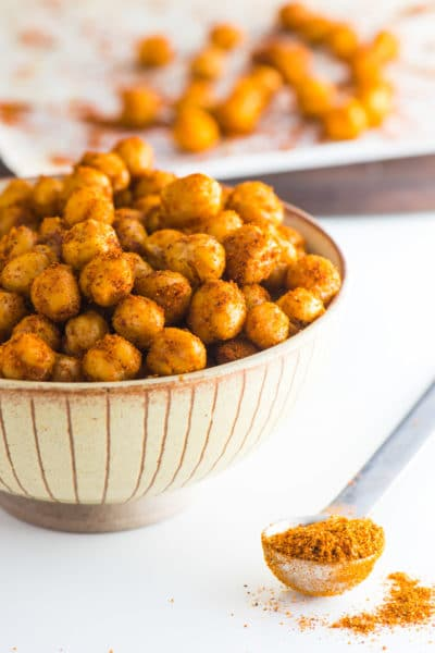 A bowl is full of roasted chickpeas with a teaspoon of seasoning beside it.
