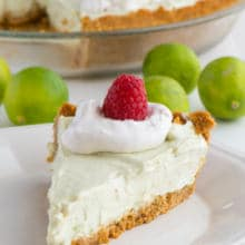 A slice of vegan key lime pie sits in front of the rest of the pie.