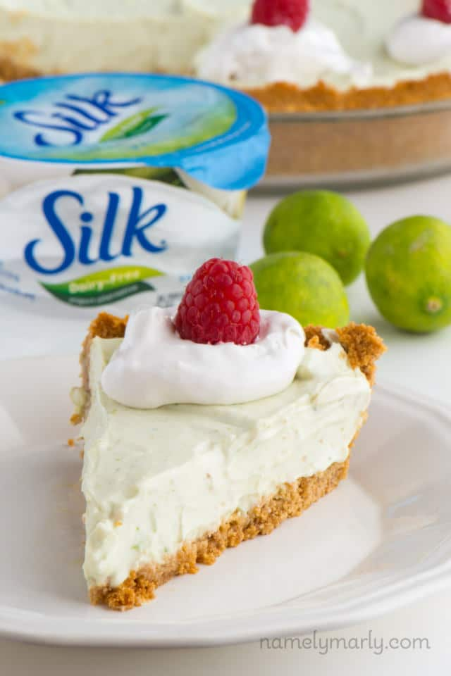 A slice of vegan key lime pie sits in front of a container of dairy-free yogurt.