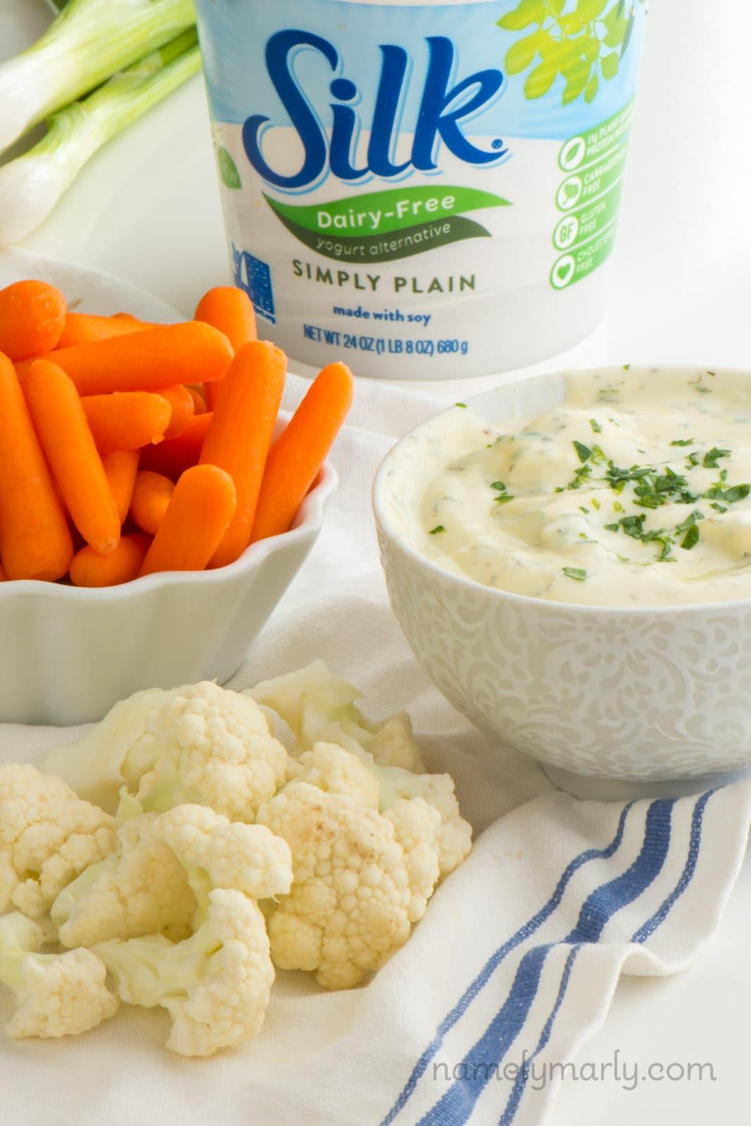 A bowl of ranch dip by cut up veggies and beside vegan yogurt.