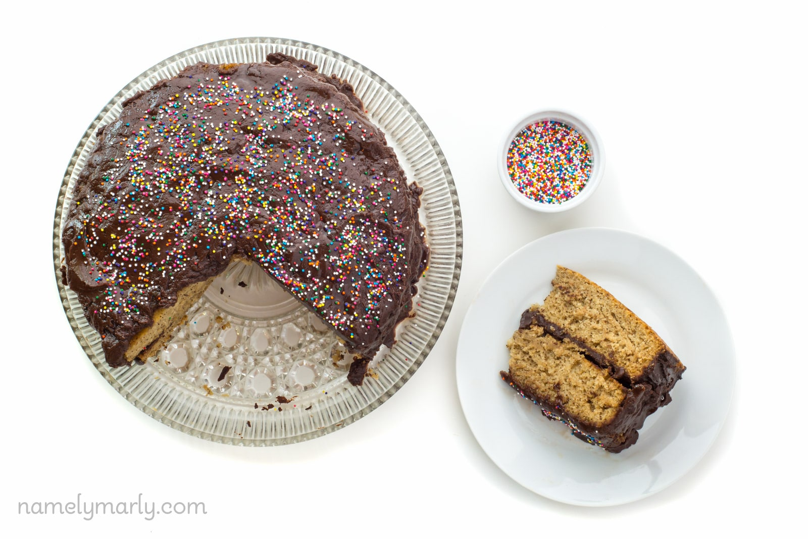 Looking down on a slice of vegan vanilla wacky cake on a plate beside the whole cake with a few slices cut out. A bowl of sprinkles sits beside the plate.