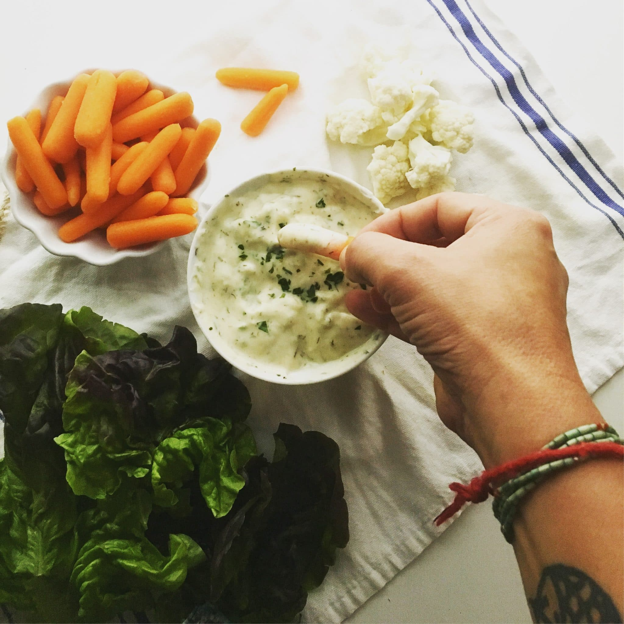 Looking down on a bowl of ranch dip and a hand reaches in to dip a baby carrot.