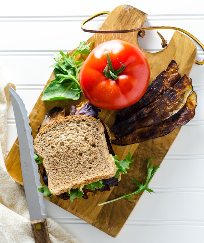 Looking down on a vegan BLT sandwich sitting on a cutting board next to vegan bacon strips, a tomato and greens.