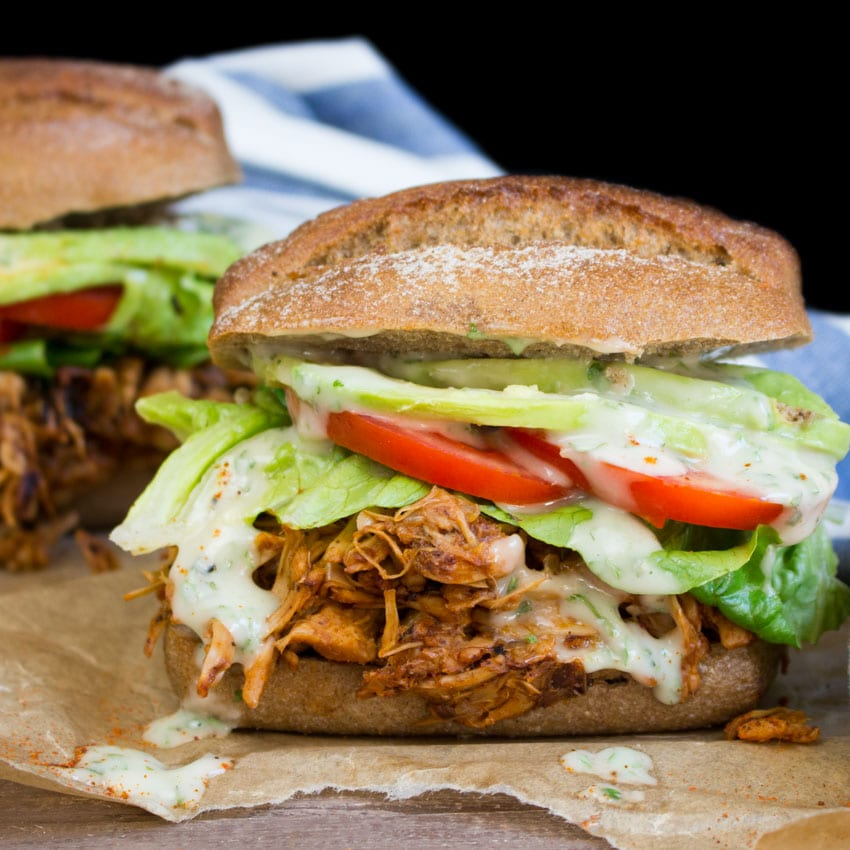 A whole wheat bun holds BBQ vegan meat with sliced tomatoes, greens, and a creamy sauce dripping over the sides.