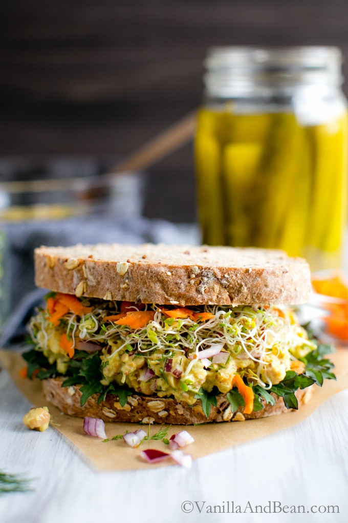 A sandwich is in the center showing sprouts, smashed chickpeas and carrots. There is a tall glass of pickles behind the sandwich.