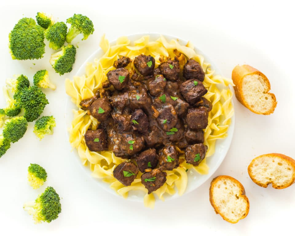 Looking down on a plate of vegan beef stroganoff, surrounded by slices of bread and steamed broccoli florets.