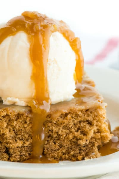 A slice of vegan cinnamon roll poke cake has a scoop of ice cream on the top and is drizzled with caramel sauce.