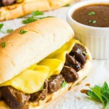 A Vegan French Dip Sandwich with melted cheese. A bowl of sauce and another sandwich is in back.