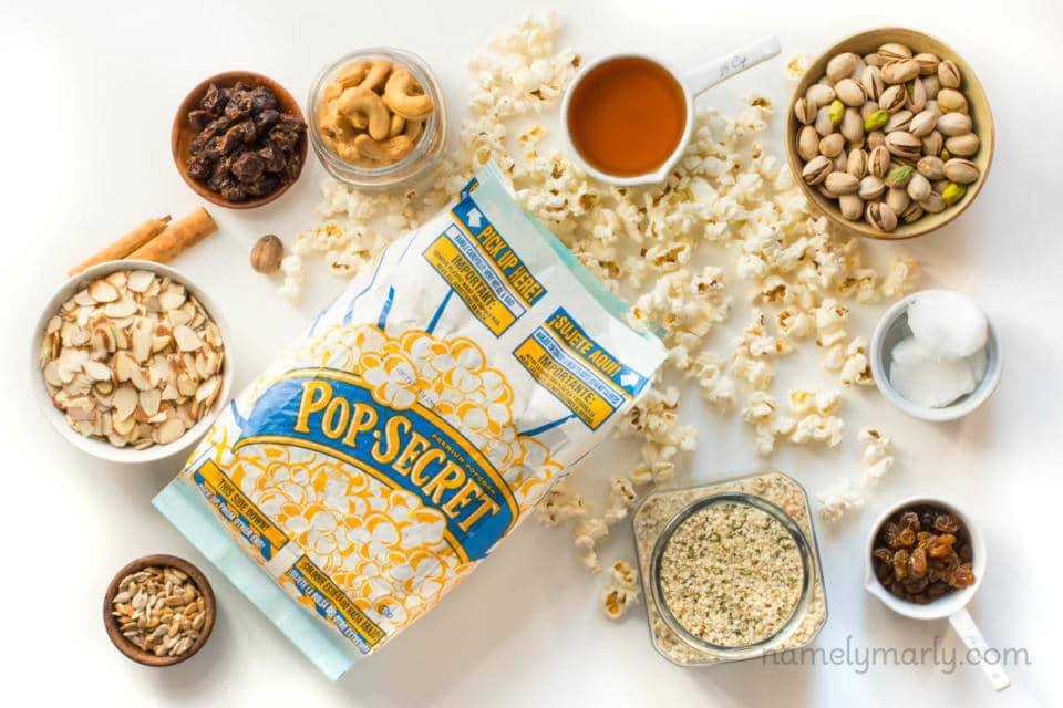 Several ingredients are on a white counter, including a bag of popped microwave-popcorn, and bowls of nuts, raisins, syrup, coconut oil, and more.