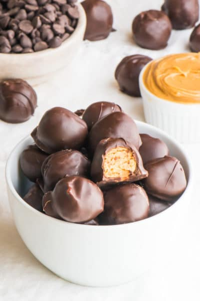 A bowl holds peanut butter balls, one with a bite taken out of it.