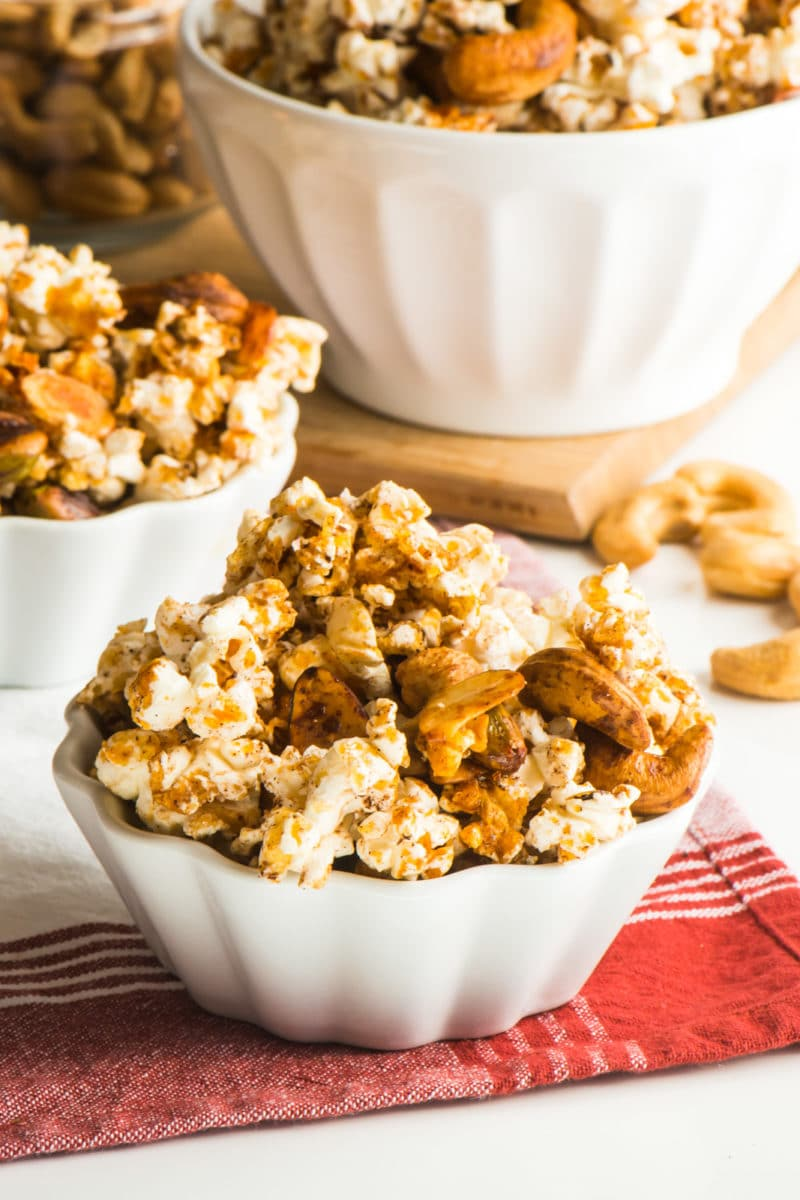 Vegan Cinnamon Popcorn Trail Mix in a small serving bowl with a larger bowl full of it behind it.